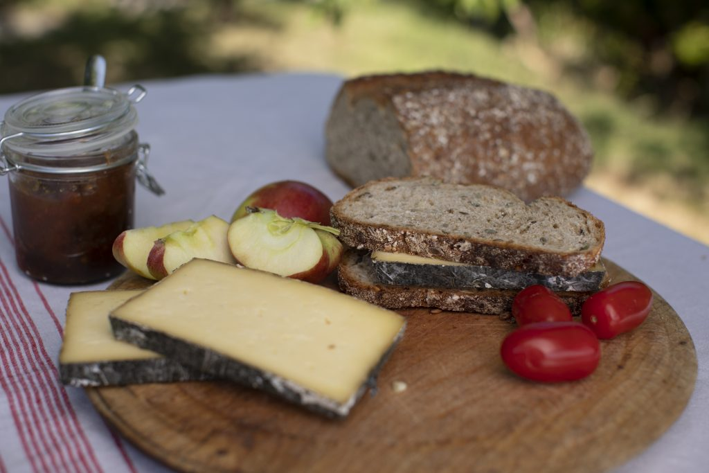 Sliced Cornish Yarg on bread board with rustic loaf in al fresco setting