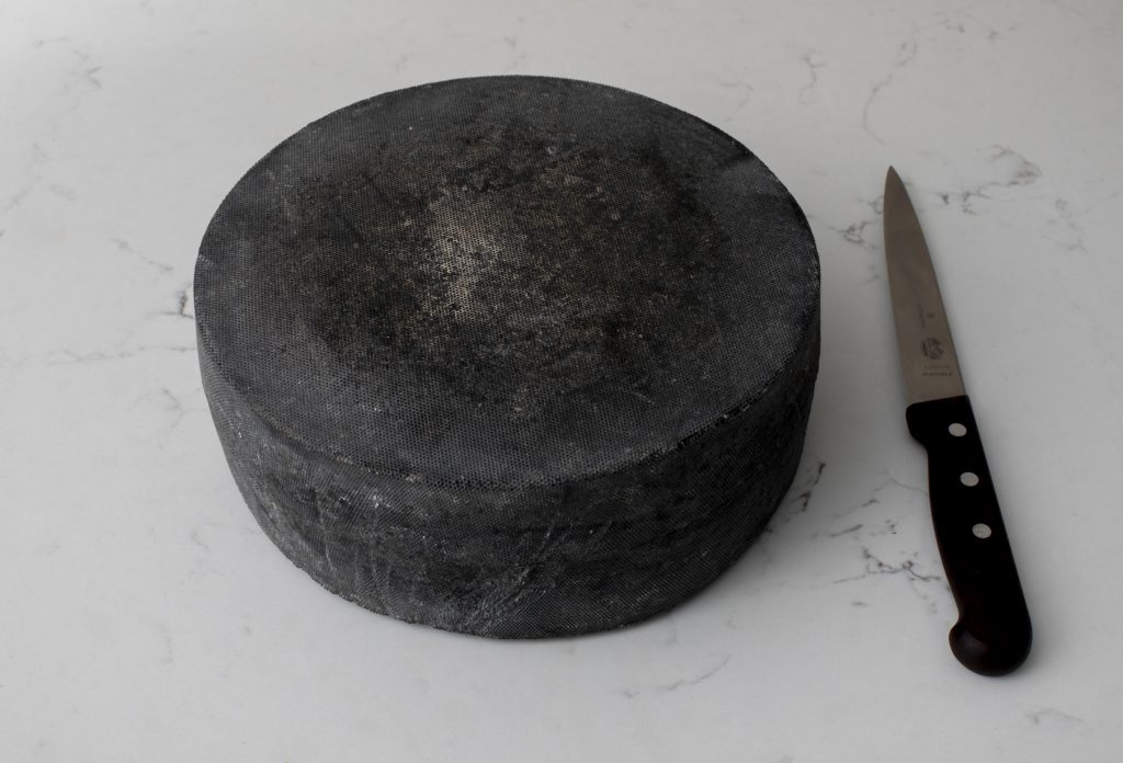 A wheel of Supreme Champion Kern before it is cut, handsome in its black waxy rind